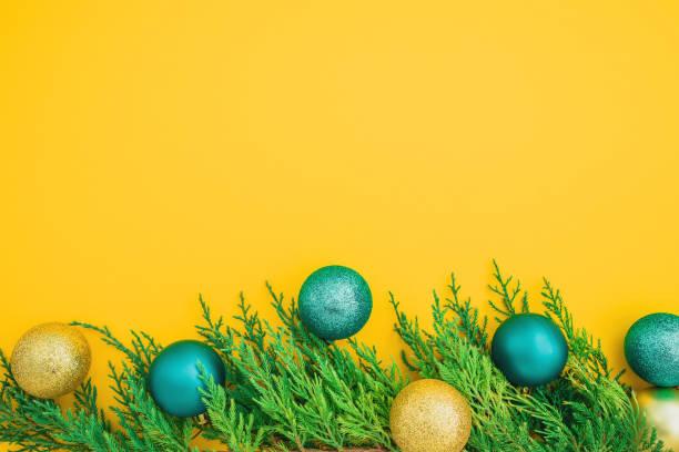 Weihnachten Winterkonzept aus immergrünen Zweigen und Bälle Dekoration auf gelbem Hintergrund. Flach liegen, Ansicht von oben. Kopierraum – Foto