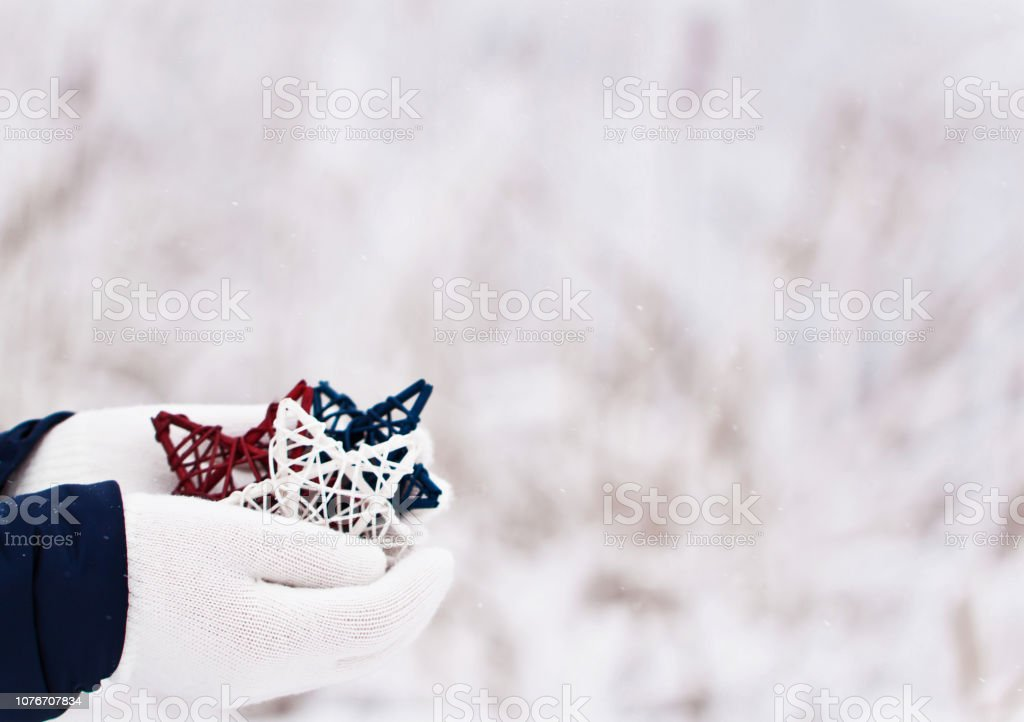 outdoor scene in falling snow of close up fo hands holding a...