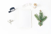istock Christmas, winter wedding desktop stationery mock-up scene. Blank greeting card, envelope, black washi tape, silk ribbon and green spruce tree branch.White table background. Flat lay, top view. 1069514760