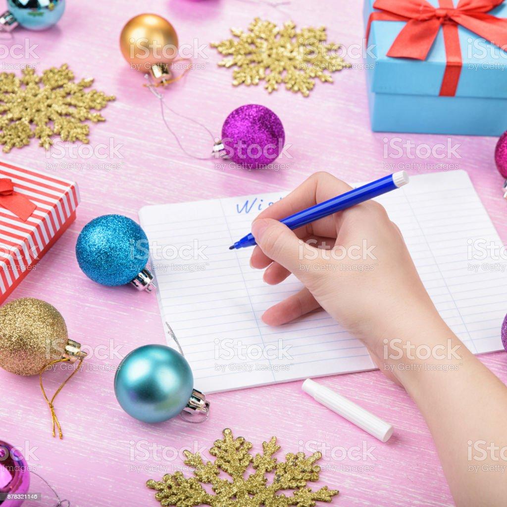 Christmas wish list on pink background. stock photo