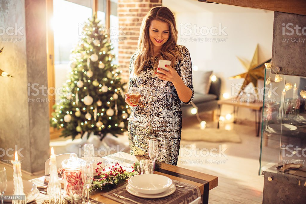 Woman holding glass of champagne and checking her phone. Standing...