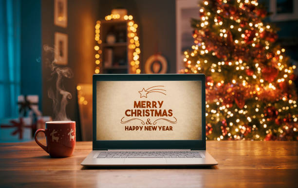 Christmas wishes on a laptop and Christmas tree stock photo