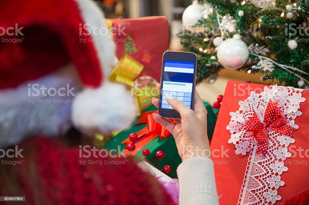 Woman using smart phone and typing Merry Christmas text message....