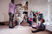 Two dads prepare and decorating the Christmas tree. One is african-american ethnicity and the other one is caucasian. The other members of the family watch them. They are in the living room.  Children wear reindeer ears. Horizontal and color Photo was taken in Quebec Canada.