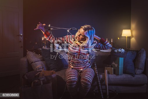 istock Christmas woman at home with christmas lights tangled 628508690