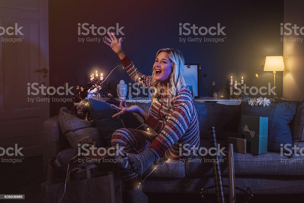 Christmas woman at home with christmas lights tangled stock photo
