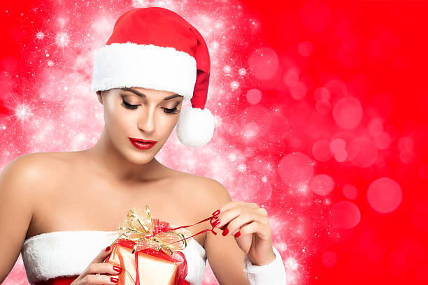 christmas woman in santa clothes unwrapping gift stock photo