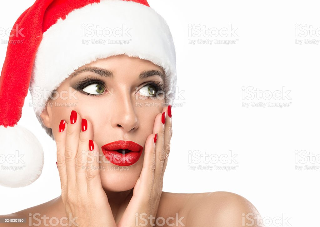 Christmas woman in Santa hat with a surprise expression isolated stock photo