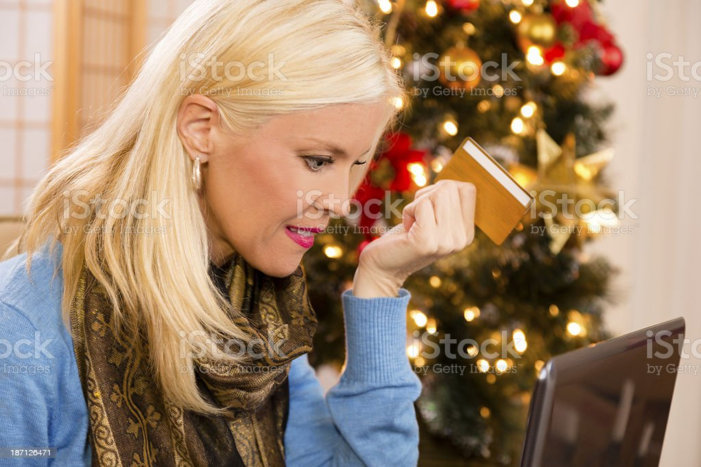 Christmas: Woman uses credit card to shop online for gifts. royalty-free stock photo