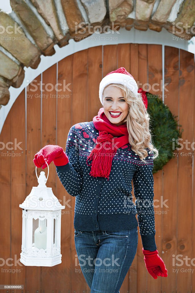Christmas Woman with Lantern Outdoor portrait of beautiful woman wearing santa hat, red scarf and gloves, holding lantern and smiling at camera. Adult Stock Photo