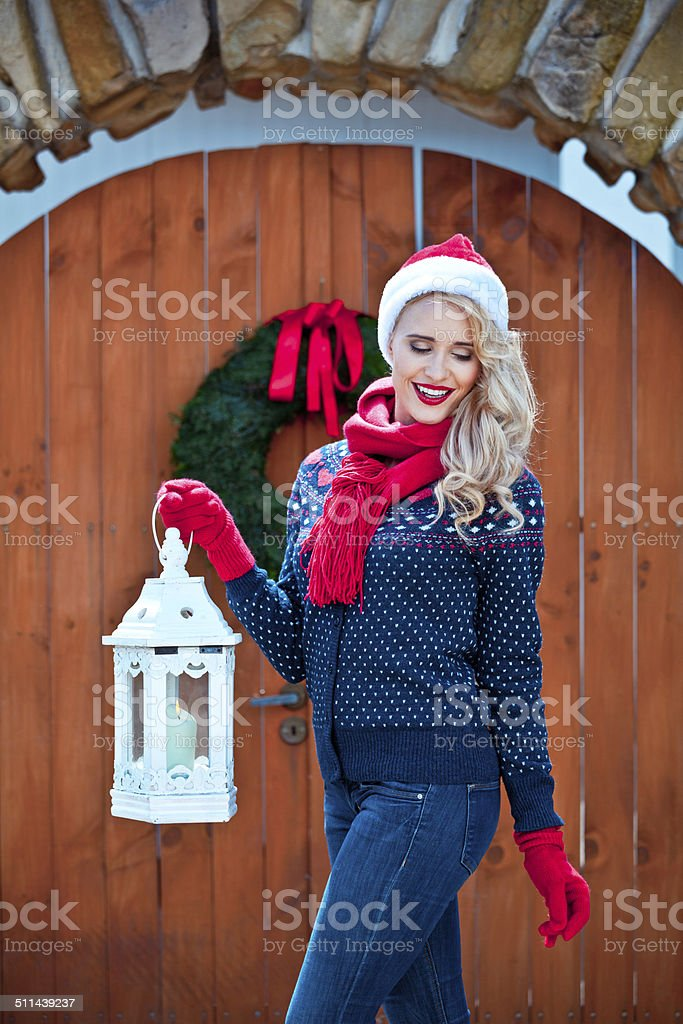 Christmas Woman with Lantern Outdoor portrait of beautiful woman wearing santa hat, red scarf and gloves, standing against entrance door decorated with christmas wreath and holding lantern. Adult Stock Photo