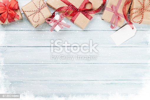 istock Christmas wooden background with gift boxes and snow 613524686