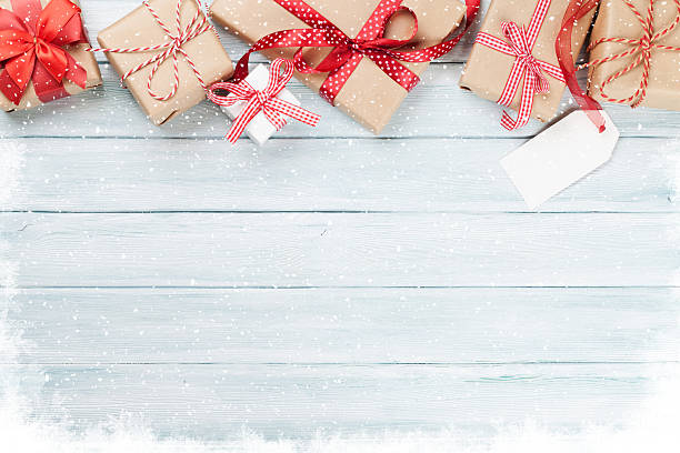 christmas wooden background with gift boxes and snow - christmas stock photos and pictures
