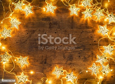 istock Christmas wooden background with lights. 636658258