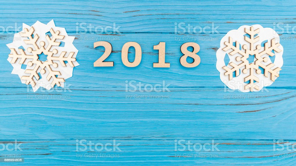 Christmas wooden snowflakes and the numbers 2018 on blue wooden old table stock photo