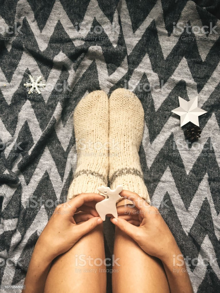Christmas woolen socks on legs and stylish reindeer toy in hands, relaxing on plaid with holiday ornaments in festive room. Top view. Atmospheric cozy image, warm winter mood – zdjęcie