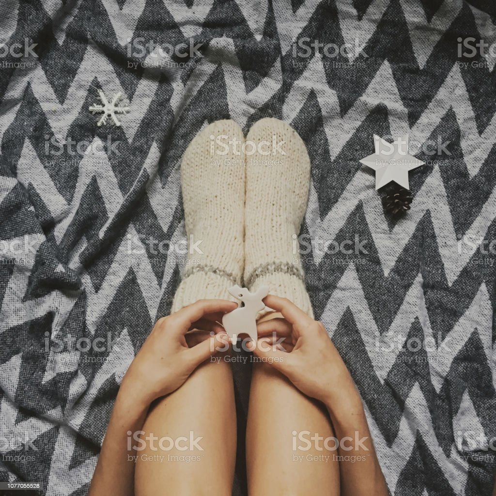Christmas woolen socks on legs and woman holding stylish reindeer toy, relaxing on plaid with holiday ornaments in festive room. Top view. Atmospheric cozy image, warm winter mood – zdjęcie
