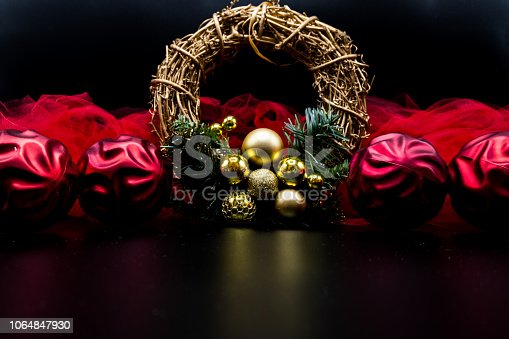 istock Christmas wreath and decorations with red balls and fabric on black. 1064847930