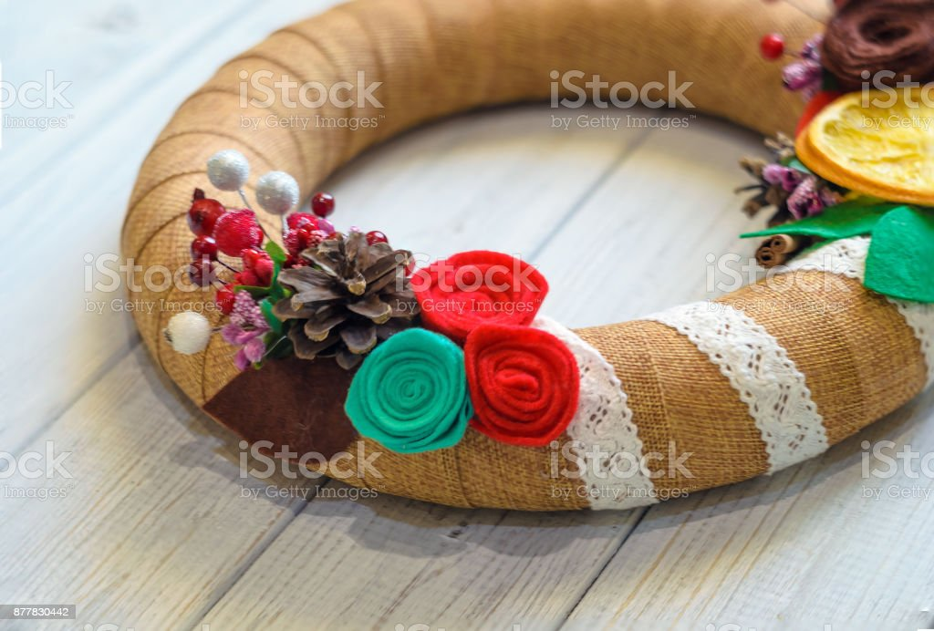Christmas wreath and ribbon bow on a wooden board background stock photo