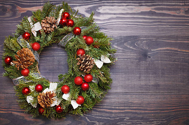 Christmas wreath and ribbon bow on wooden background stock photo