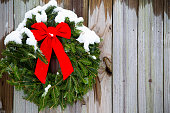 A Christmas pine wreath background with red bow hung in a winter snow storm on rustic barn wood with copy space.