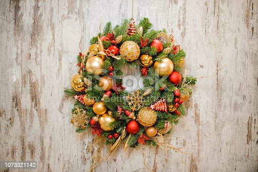 istock Christmas wreath decorated with red and golden bulbs 1073321142