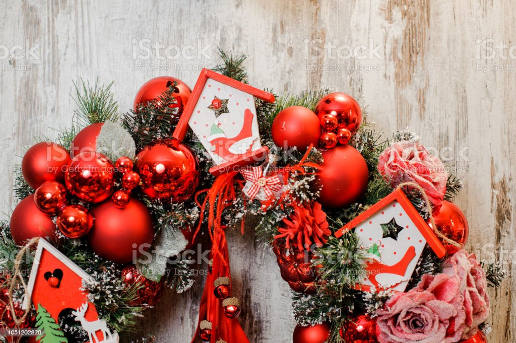 Bright Christmas Wreath decorated with red balls, roses and toy...