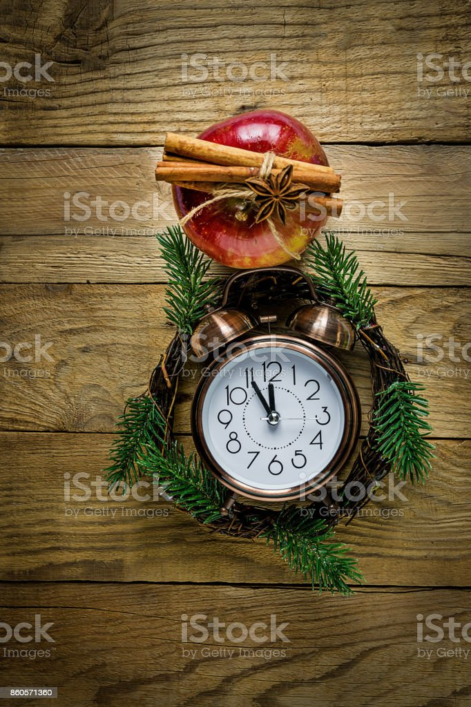 Christmas Wreath Fir Tree Branches Vintage Alarm Clock Red Glossy Apple Cinnamon Sticks Anise Star on Weathered Wood Background. Magic Cozy Atmosphere. New Years Greeting Card. Copy Space stock photo