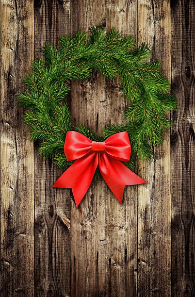 christmas wreath from pine twigs and red ribbon bow - türbänder stock-fotos und bilder