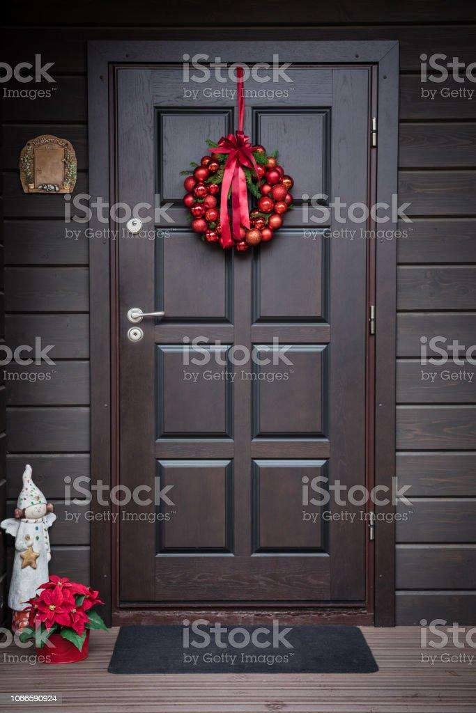 Christmas wreath hanging on a wooden door, toned