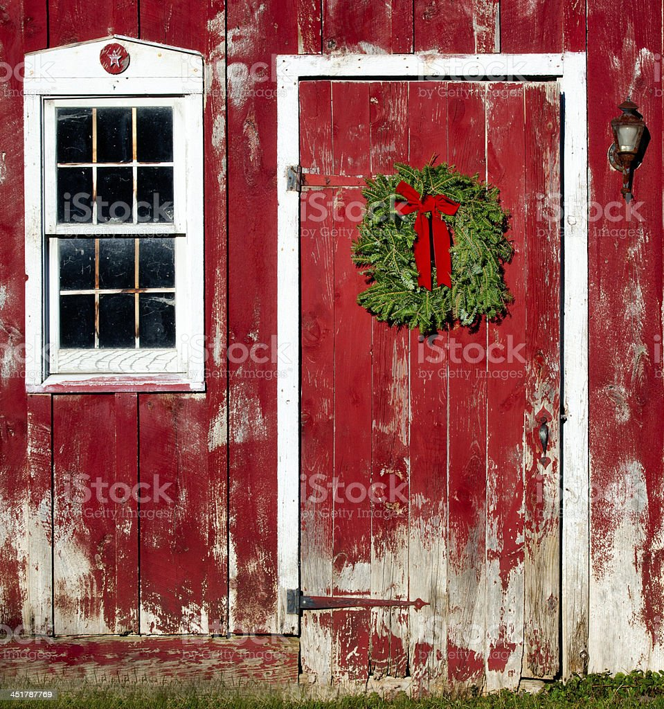 Christmas Wreath hanging on Red Barn Door stock photo