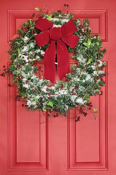 christmas wreath hanging on red front door - türbänder stock-fotos und bilder