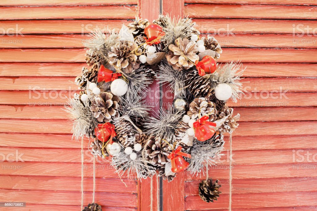 Christmas wreath hanging on wooden blinds stock photo