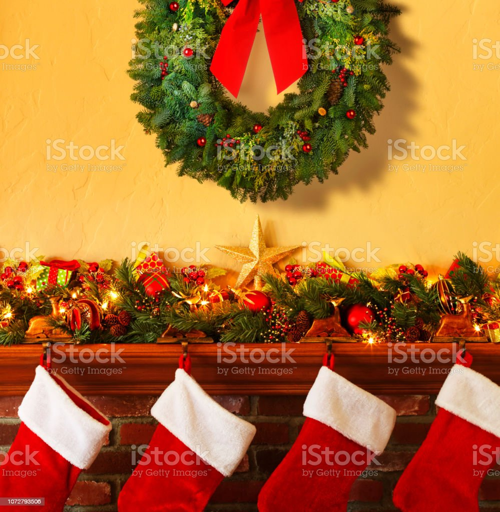 Christmas Wreath Hangs Above Christmas Decorated Mantelpiece And Four Stockings stock photo