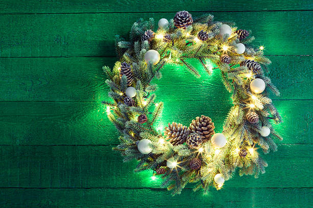 Christmas wreath lighting a green wooden surface stock photo