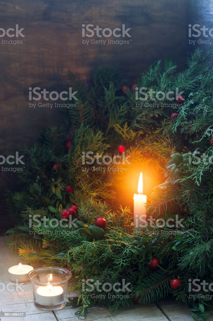 A Christmas wreath made of fir branches, juniper, tuja, boxwood and wild rose berries. Wreath with burning candles. stock photo