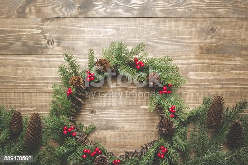 istock Christmas wreath of spruce branches with holly berries on wooden board. Flat lay. Top view. Toned image. 889470562