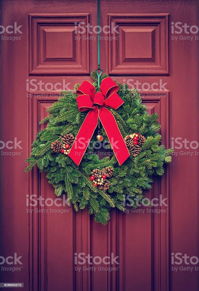 Christmas wreath on a red door bildbanksfoto