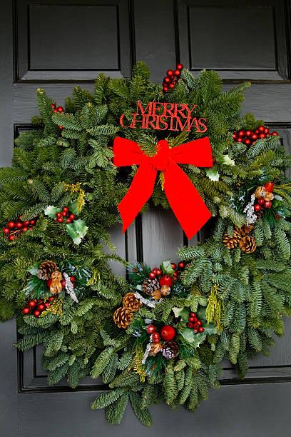 weihnachten kranz auf schwarzen tür - buchstabentür kränze stock-fotos und bilder