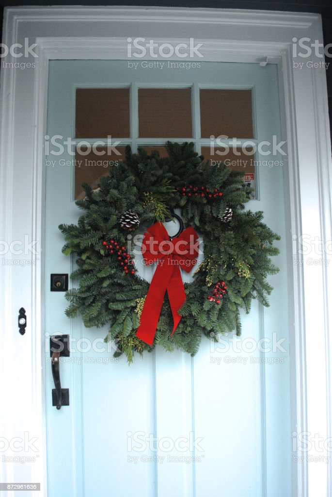 Evergreen Christmas wreath with red bow on blue front door