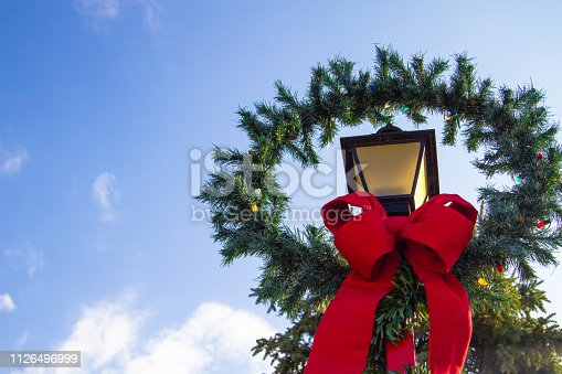 Pine tree with fresh fallen snow and multi colored Christmas bulbs in horizontal orientation with copy space.
