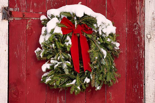 weihnachten kranz auf roten farmtor und frischem schnee - türbänder stock-fotos und bilder