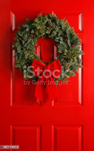 A Christmas wreath hanging on a red door.To see more holiday images click on the link below: