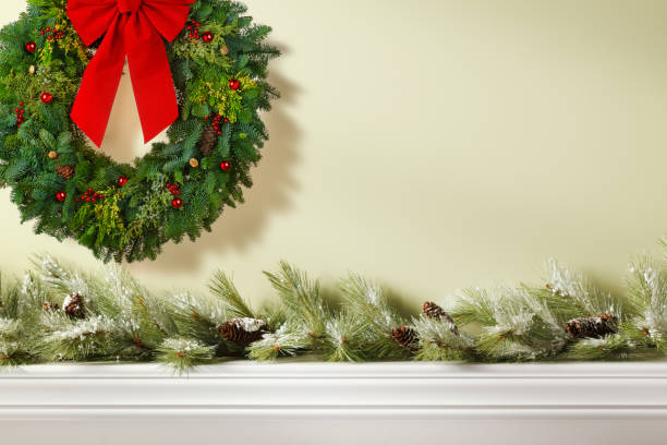 christmas wreath over mantelpiece adorned with christmas garland - garland decoration stock photos and pictures
