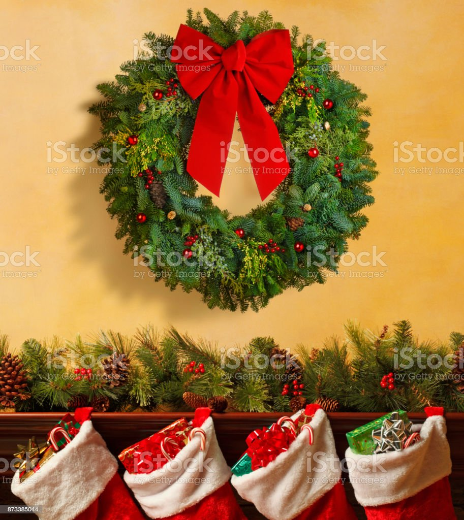 Christmas Wreath Over Mantelpiece Adorned With Christmas Garland Stock  Photo - Download Image Now