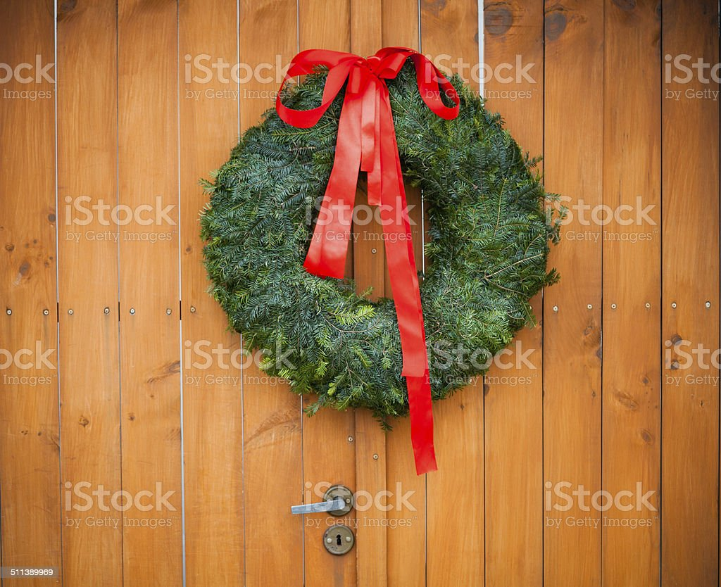 Christmas wreath Close up of door decorated with christmas wreath. Branch - Plant Part Stock Photo