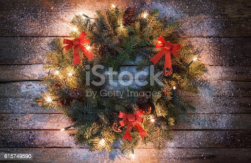 Christmas wreath on the old wooden background covered with snow
