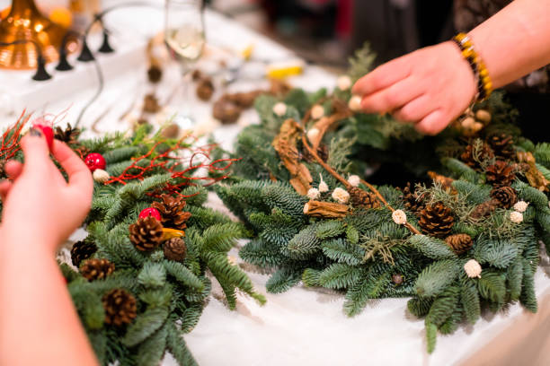 christmas wreath weaving workshop. woman hands decorating holiday wreath made of spruce branches, cones and various organic decorations on the table - making stock pictures, royalty-free photos & images