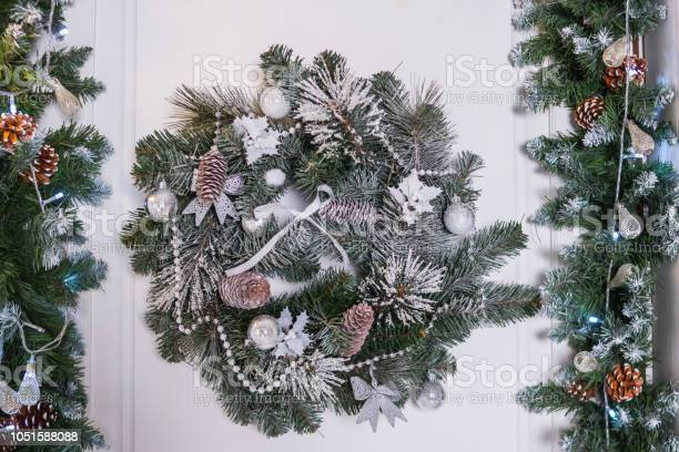 Photo of Christmas wreath with baubles, cones and evergreen boughs on a white door.Wreath decoration at door for Christmas holiday.entrance to home with holiday wreath. House decoration.
