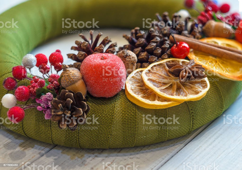 Christmas wreath with cinnamon, cone and dried orange on wooden table stock photo